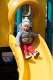 One year old baby boy toddler at playground slide. Portrait of toddler child wearing vest jacket outdoors. One year old baby boy at playground slide Royalty Free Stock Photo