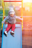 One year old baby boy toddler at playground slide. Portrait of toddler child wearing vest jacket outdoors. One year old baby boy at playground slide Royalty Free Stock Photos