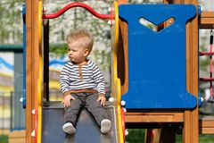 One year old baby boy toddler at playground slide. Portrait of toddler child outdoors. One year old baby boy at playground slide Stock Photo