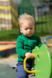 One year old baby boy toddler wearing green sweater at playground Stock Photos