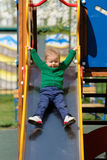 One year old baby boy toddler wearing green sweater at playground Stock Image