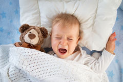 One year old baby crying. In bed with a teddy bear Stock Photo
