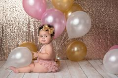 One Year Old Baby Girl with Balloons. A one year old, baby girl sitting with a bunch of balloons. She is wearing pink bloomers, a gold, sequin headband and a stock images
