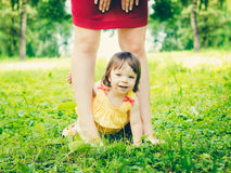 One-year old baby girl between mother legs outdoors Royalty Free Stock Images