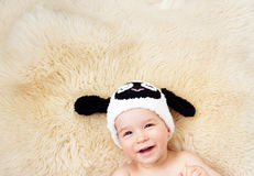 One year old baby lying in bunny hat on lamb wool stock image