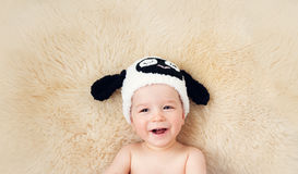 One year old baby lying in sheep hat on lamb wool Stock Images