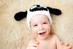One year old baby lying in sheep hat on lamb wool Stock Photos