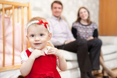 One year old baby in red dress with parents are on background Royalty Free Stock Photos