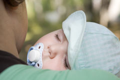 One-year-old baby sleeping on shoulder of mother Royalty Free Stock Image