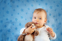 One year old baby with a teddy bear. One year old baby lying in bed with a plush teddy bear royalty free stock image