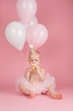 One Year Old Birthday Girl Eating a Cupcake. A portrait of a one year old baby girl wearing a pink tutu, string of pearls and birthday hat. She is sitting and Royalty Free Stock Photo