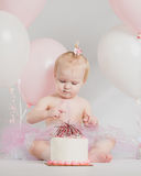 One Year Old Birthday Portraits With Smash Cake. Adorable one year old little girl birthday portrait white background looking at smash cake royalty free stock image