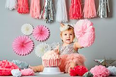 One Year Old Birthday Portraits with smash cake. Baby girl and her birthday cake doing a smash cake in a studio royalty free stock photos