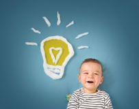One year old boy and a bulb near. Child with an idea Royalty Free Stock Image