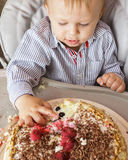 One year old boy celebrating his first Birthday. One year old boy is sitting in high chair and tasting his cake. First Birthday celebrating concept. Cake smash Stock Photography