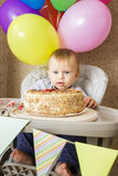 One year old boy celebrating his first Birthday. One year old boy is sitting in high chair and tasting his cake. First Birthday celebrating concept. Cake smash Royalty Free Stock Photos