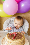 One year old boy celebrating his first Birthday. One year old boy is sitting in high chair and tasting his cake. First Birthday celebrating concept. Cake smash Royalty Free Stock Image