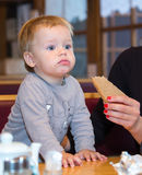 One year old boy eating rye-bread in cafe. From mothers hand Royalty Free Stock Photography