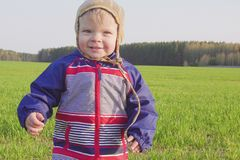 One year old boy farmer standing in the field with young wheat.  stock image