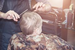 One year old boy for the first time makes the haircut in a Barber shop Royalty Free Stock Images