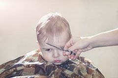One year old boy for the first time makes the haircut in a Barber shop Royalty Free Stock Photos