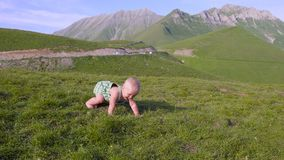 One year old boy learn to walk on the background of mountains stock footage