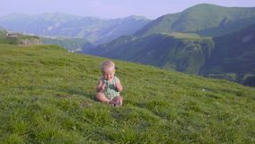 One year old boy learn to walk on the background of mountains stock video footage