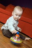 One year old boy playing with his spinning top. Cute caucasian baby boy (one year old) sitting on the floor and playing with his spinning top Stock Photo