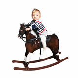 One year old boy riding on rocking horse Stock Photo