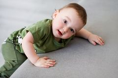 One-year-old boy tries to climb. On a gray sofa stock images
