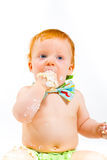 One Year Old Cake Smash. A baby boy gets to eat cake for the first time on his first birthday in this cake smash in studio against a white background stock image