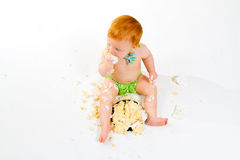 One Year Old Cake Smash. A baby boy gets to eat cake for the first time on his first birthday in this cake smash in studio against a white background stock photos