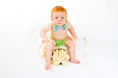 One Year Old Cake Smash. A baby boy gets to eat cake for the first time on his first birthday in this cake smash in studio against a white background stock images