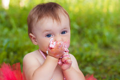 One year old child eating her first birthday cake. And express funny emotion Stock Photography
