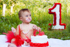 One year old child eating her first birthday cake Stock Image
