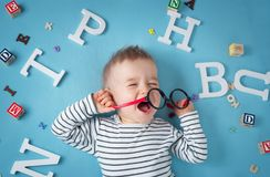 One year old child lying with spectacles and letters. On blue background royalty free stock photo