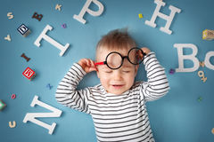 One year old child lying with spectacles and letters Stock Photos