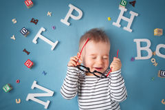 One year old child lying with spectacles and letters Stock Images