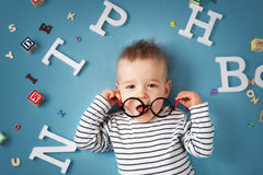 Free One Year Old Child Lying With Spectacles And Letters Royalty Free Stock Photo - 69322475