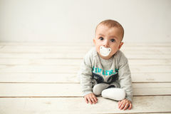 One year old cute baby boy sitting on wooden floor Stock Images