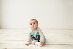 One year old cute baby boy sitting on wooden floor Royalty Free Stock Photos