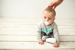 One year old cute baby boy sitting on wooden floor Stock Image