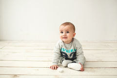 One year old cute baby boy sitting on wooden floor Royalty Free Stock Photography