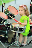 One year old cute girl in a green romper learning how to play drums Stock Images