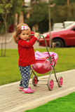 One year old cute little curly girl wearing red cardigan and a headband with a bow with a toy pink stroll in the par Stock Photos