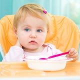 One year old girl in a highchair for feeding Stock Photos