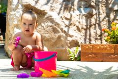 One year old girl in a pink bathing suit plays with beach toys. royalty free stock photography