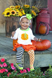 One year old girl with pumpkins and flowers. Beautiful little mixed race baby girl sitting on old wooden porch with colorful pumpkins and flowers Royalty Free Stock Photo