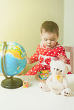 A one-year-old girl in a red dress is sitting at a table with a book, a globe and a teddy bear. Stock Image