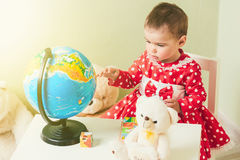 A one-year-old girl in a red dress is sitting at a table with a book, a globe and a teddy bear. Stock Photos